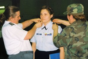 Photo by Lt. Col. Connie King - Lt. Col. Julie Sorenson (left) puts the officer epaulets on Cadet Alyssa Polasky with Maj. Tamara Winke (right).