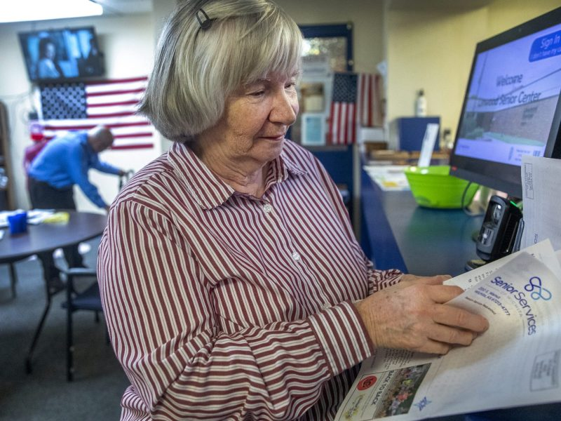 Diane Pope, who attends the Linwood Senior Center, reads the senior center's newsletter. (Alex Unruh/The Beacon)
