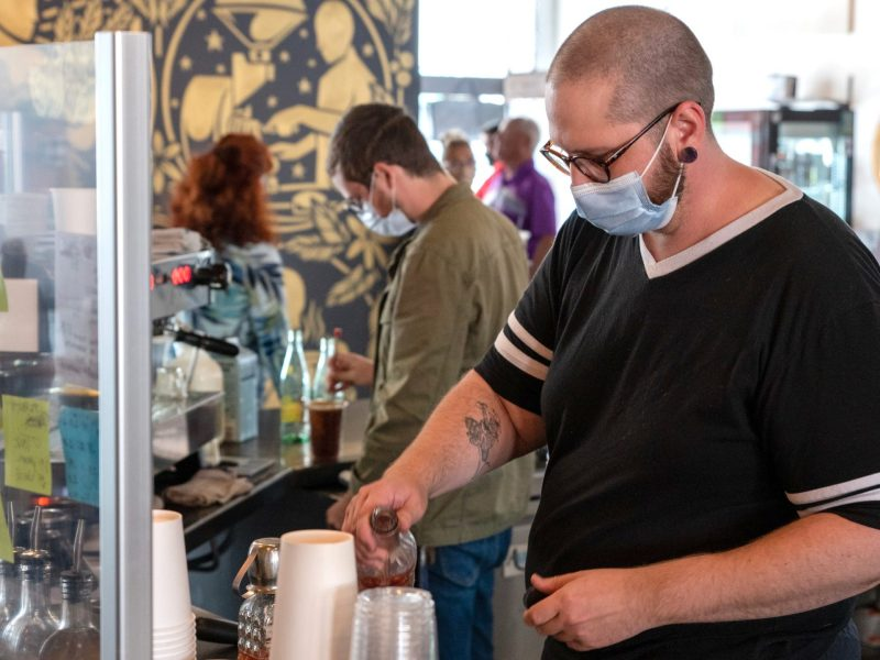 Employees at some local businesses — including Kyle Borger at Reverie Roasters, pictured here — choose to wear one. (Alex Unruh/The Beacon)