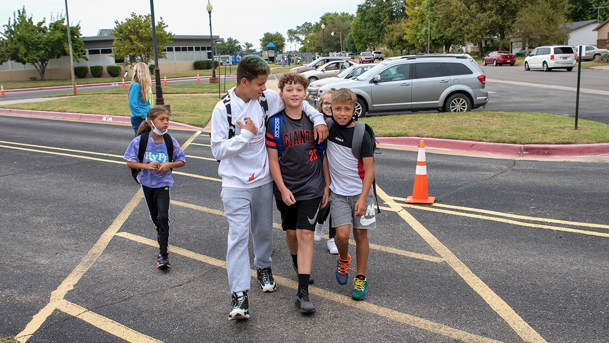 Terrance Brobst wraps his arm around friend Jackson Fasig as they walk out of Nelson Elementary School on Oct. 1. Walking to school together is one of the pair's favorite parts of their mornings. (Alex Unruh/The Beacon)