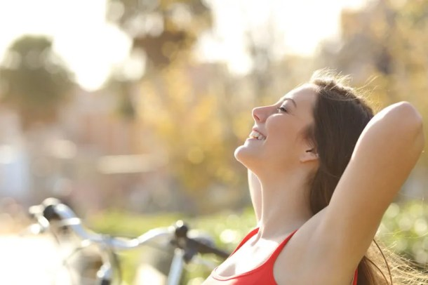 Happy woman with a bike in a park