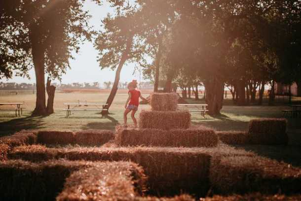 Playing on the hay bales at Cedar Creek Farm and Pumpkin Patch in Maize, KS