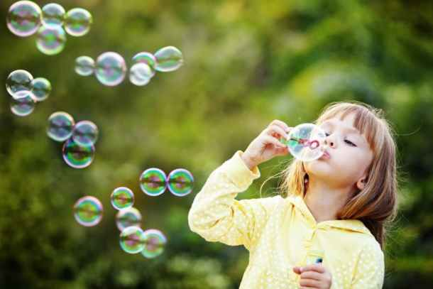 Summer fun for kids playing outdoors blowing bubbles