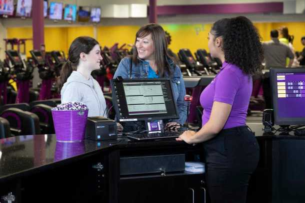 Teen girl with a parent signing up in person for the Planet Fitness Teen Summer Challenge