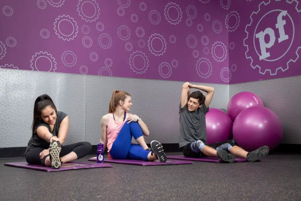 Teens stretching on mats during a free fitness class offered by Planet Fitness Teen Summer Challenge