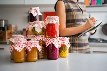 Preserved homegrown food in canning jars on kitchen counter, woman in the background making notes