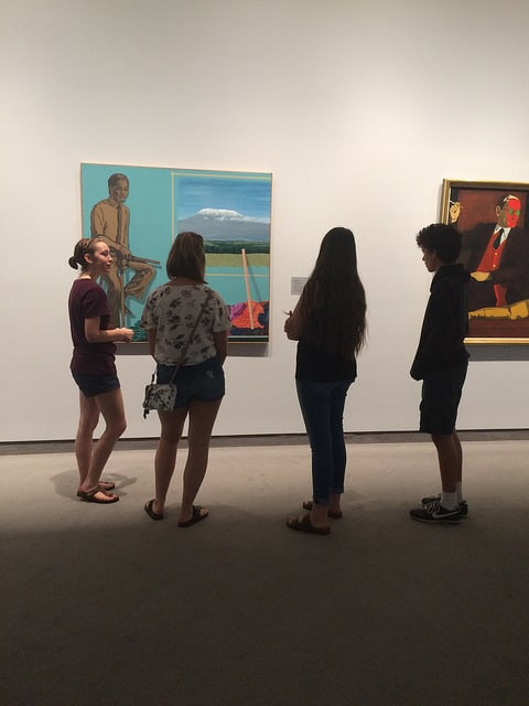 Young people looking at a piece of art hanging on the wall of the Wichita Art Museum