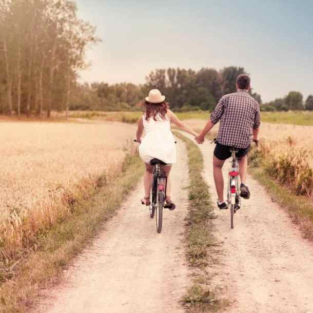 Ideas for date night wichita ks - couple on a date bicycling down a dirt road