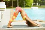 Woman doing yoga by the swimming pool