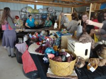 Sara and guild members with a black alpaca fleece (or blanket); retail opportunity in the foreground!