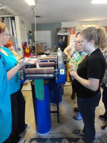 Explaining how the draw frame works to draft fiber in the final step before spinning.