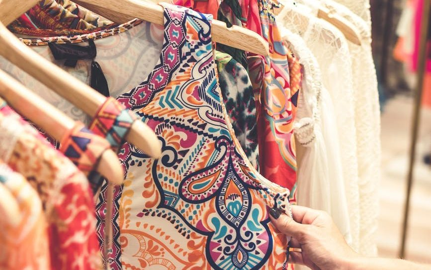 shallow focus photography of assorted color clothes hanged on clothes rack