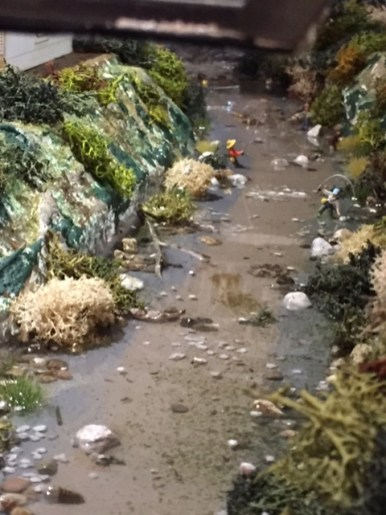 River with real rocks and fisherman