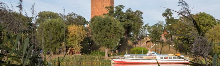 Widok przez jezioro Gopło na Mysią Wieżę i statek wycieczkowy