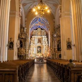Katedra w Kaliszu, wnętrze nawy głównej. Dwa rzędy ławek, ołtarz, oświetlenie żyrandolem.