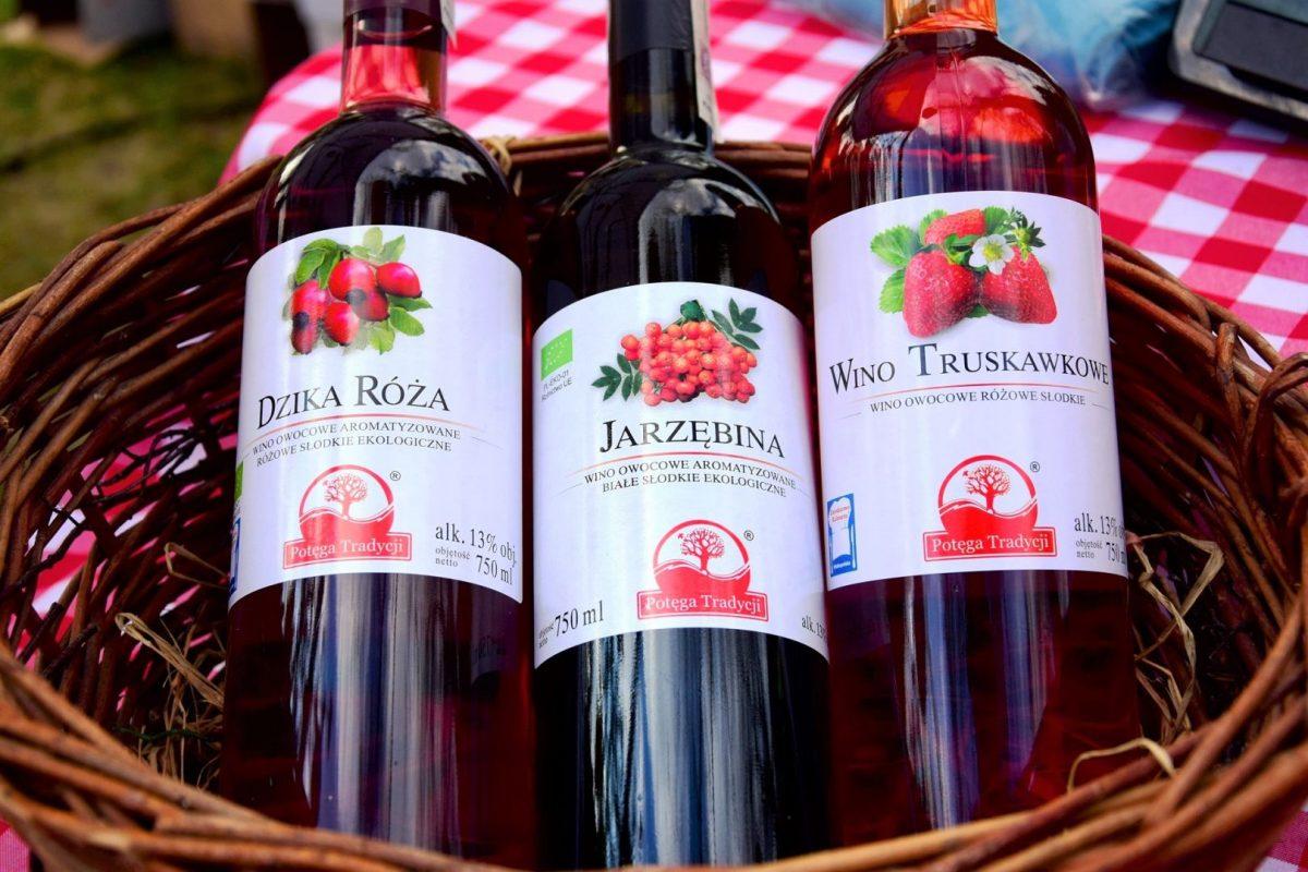 Trzy butelki wina owocowego w koszyku