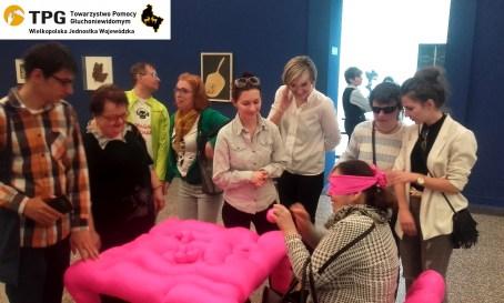 """Na pierwszym planie instalacja """"Dotykotki"""" - Ania siedzi na materiałowym, różowym krześle z zasłoniętymi oczami, dotyka ruchomych części stojącego przed nią stołu, również z różowego materiału - lycry. Za nimi stoi grupa osób."""