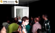 Na pierwszym planie grupa osób, w tle zawieszona instalacja Bez Tytułu - podświetlona skrzynka, wyłożona białymi otoczakami. Wewnętrz sześciennej kostki widać głowę Joli, która zagląda do niej, wkładając głowę od dołu.