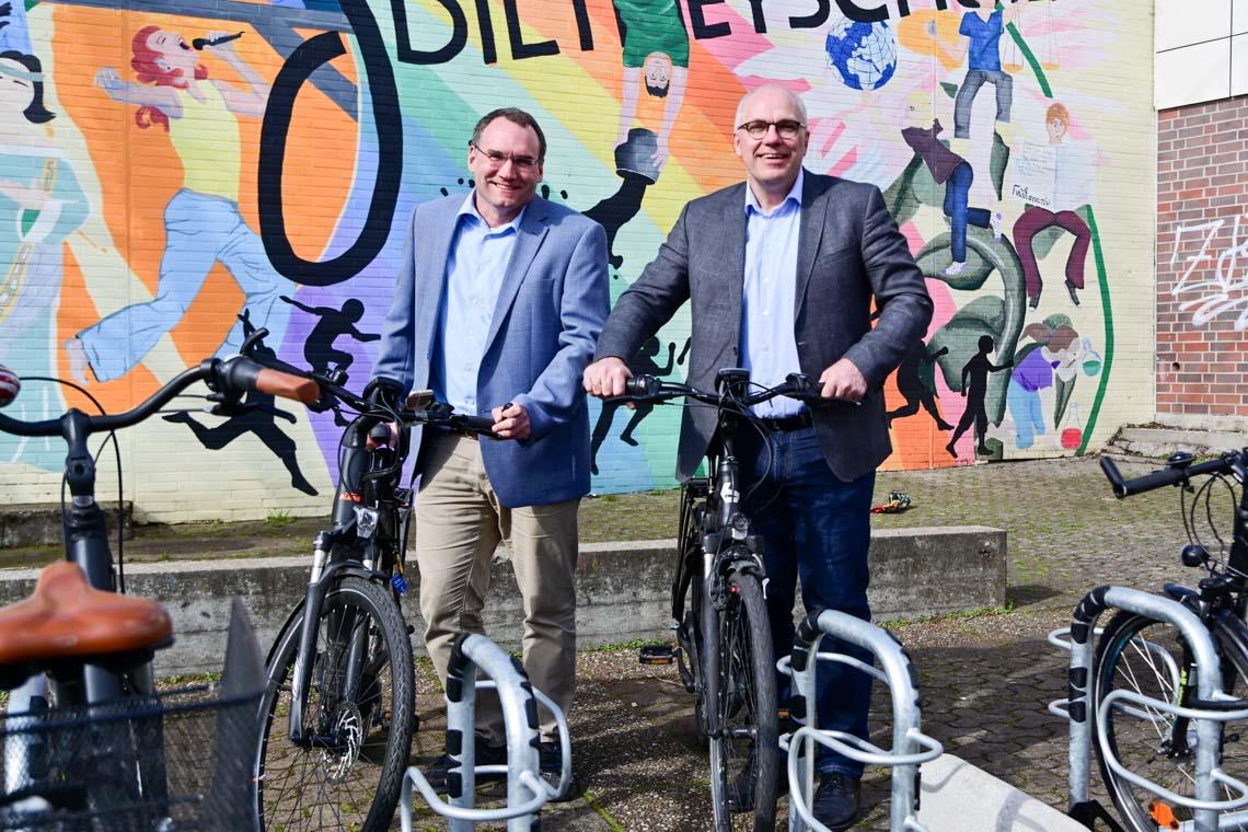 Schulleiter Jörg Schulte (re) und sein Stellvertreter Dr. Frank Becker stellen Räder in den neuen Fahrradständer.