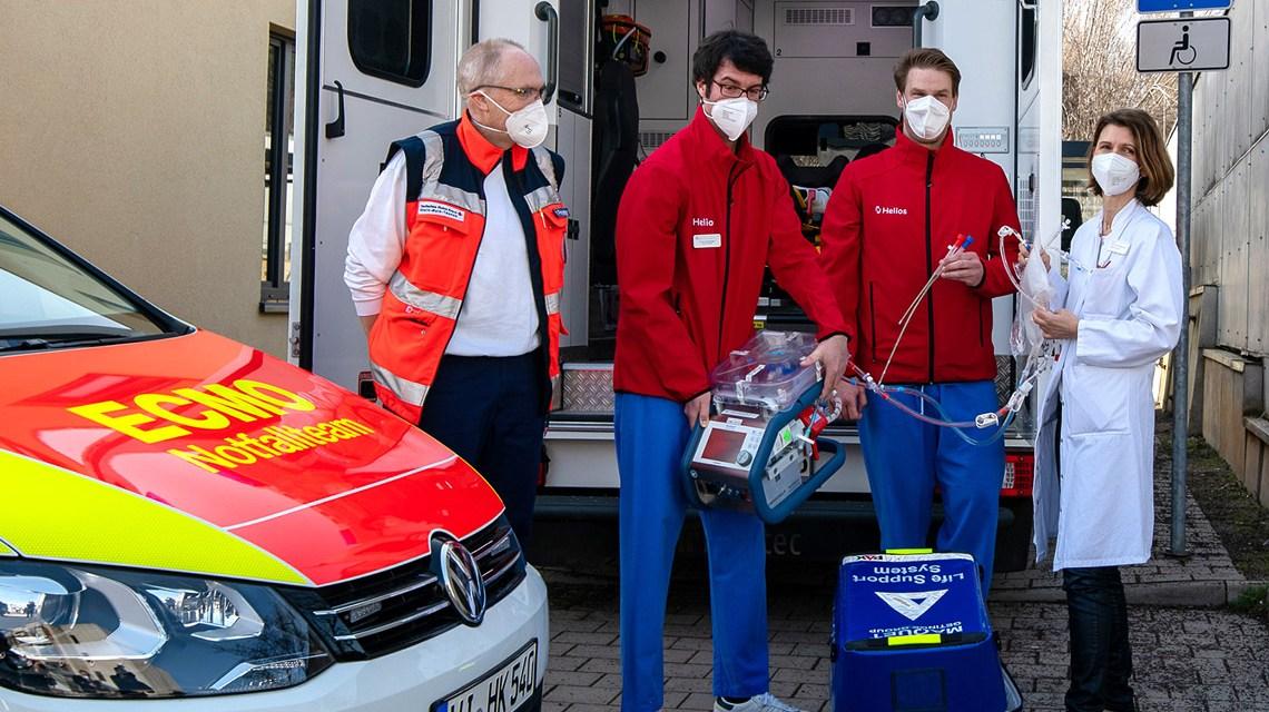 ECMO-Team I: (v.l.n.r) Rettungssanitäter, Dr. Ralf Schneider, Dr. Moritz Unglaube und Prof. Dr. Grietje Beck mit dem mobilen ECMO-Gerät ECMO-Team II: (v.l.n.r.): Dr. Ralf Schneider, Dr. Moritz Unglaube und Prof. Dr. Grietje Beck von den Helios HSK erläutern die Funktionsweise des mobilen ECMO-Geräts vor dem ECMO Fahrzeug