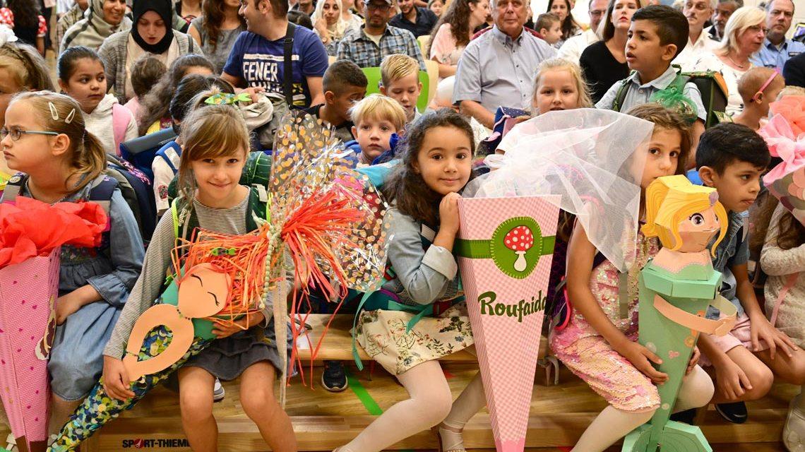 Schulstart: Erstklässler sitzen in der ersten Reihe, dahinter die Eltern in der Turnhalle der Freiherr-vom-Stein Schule