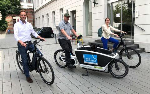 Felix Pohl, Jean Amend mit Hund Agilo und Christina Schröder aus dem IHK-Team bei der Übernahme der Räder. ©2021 IHK Wiesbaden