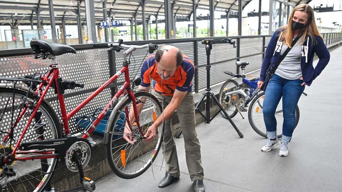 Der Radler, Mann baut an einem Fahrrad das Vorderrad aus.
