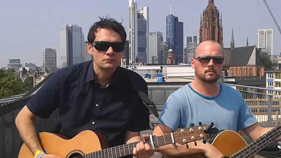 Tilman Birr und Elis singen Welthits auf Hessisch vor der Frankfurter Skyline.