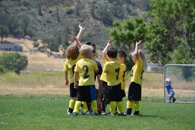 Kinderfußballteam in Dressen klatscht sich ab.