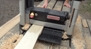 The thick planks are planed down to the right thickness using an electric planer. Wayne and his crew completed some of this work outside on the Lac du Flambeau reservation, but the rest of the process is being done at the wood studio at the University of Wisconsin-Madison's Art Department (Photo Credit: Thomas A. DuBois)
