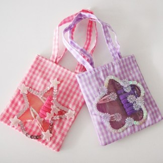 Detská luxusná kockovaná taštička pre malé princezné sa vždy hodí. Obsahuje gumičky s ozdobou a sponky. Je praktická a vyrobená z výborného materiálu.Farba- fialová. Rozmer: 10cm x 21cm.