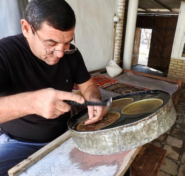 An artisan chiseling a souvenir plate in Bukhara, Uzbekistan