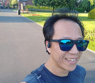 Running through park wearhing Aftershokz Aeropex and sunglasses