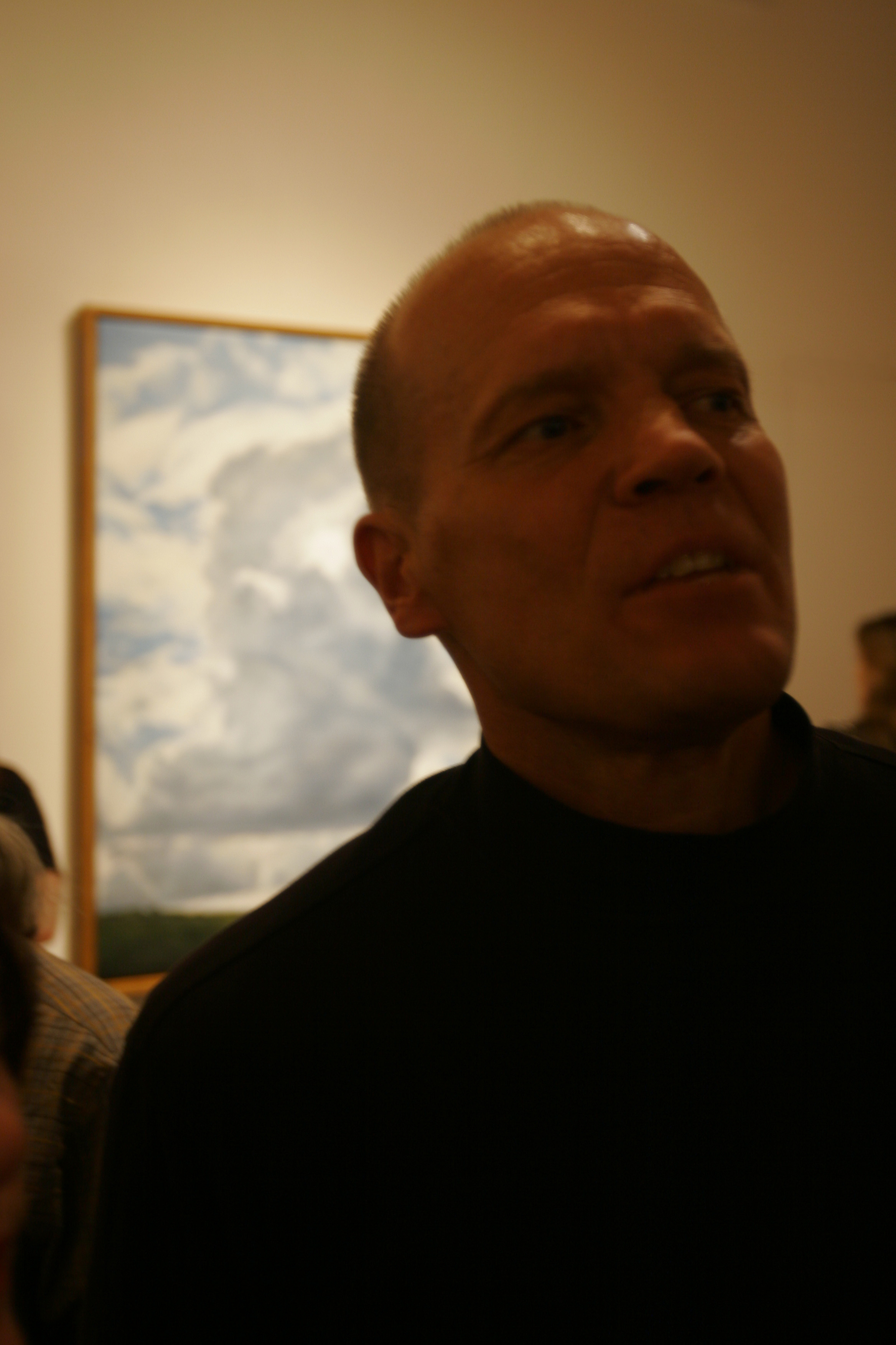 "Clifford Smith at his opening reception in front of his oil painting ""Vertical Cumulus Cloud"""