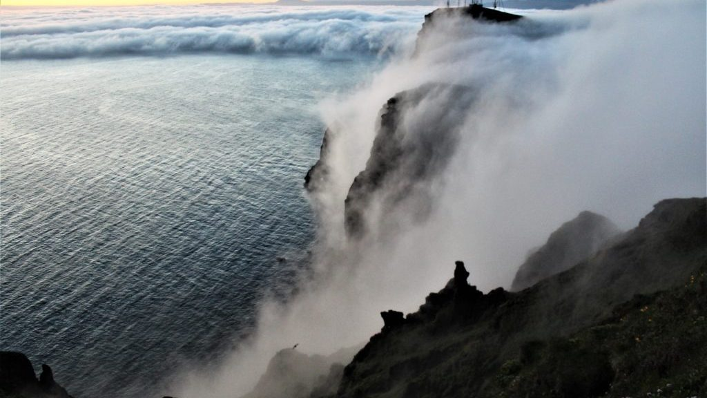 Fog waterfalls pouring over the cliffs, Heimaey, Vestmannaeyjar, Iceland