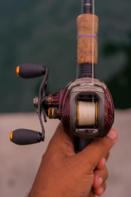 a man holding a baitcasting reel