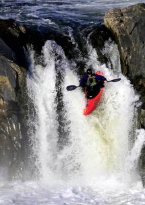 Kayaker traversing a waterfall