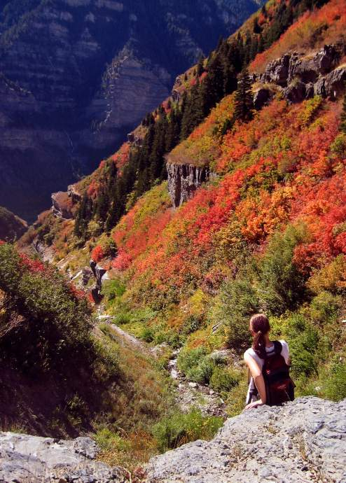 A hiker sits on the edge of a waterfall in Slide Canyon.