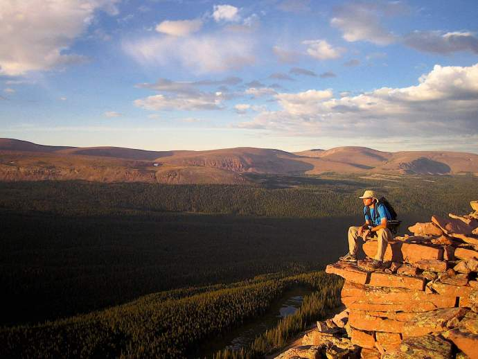 A hiker watches the sun set from a remote ridge top in the High Uintas Wilderness Area
