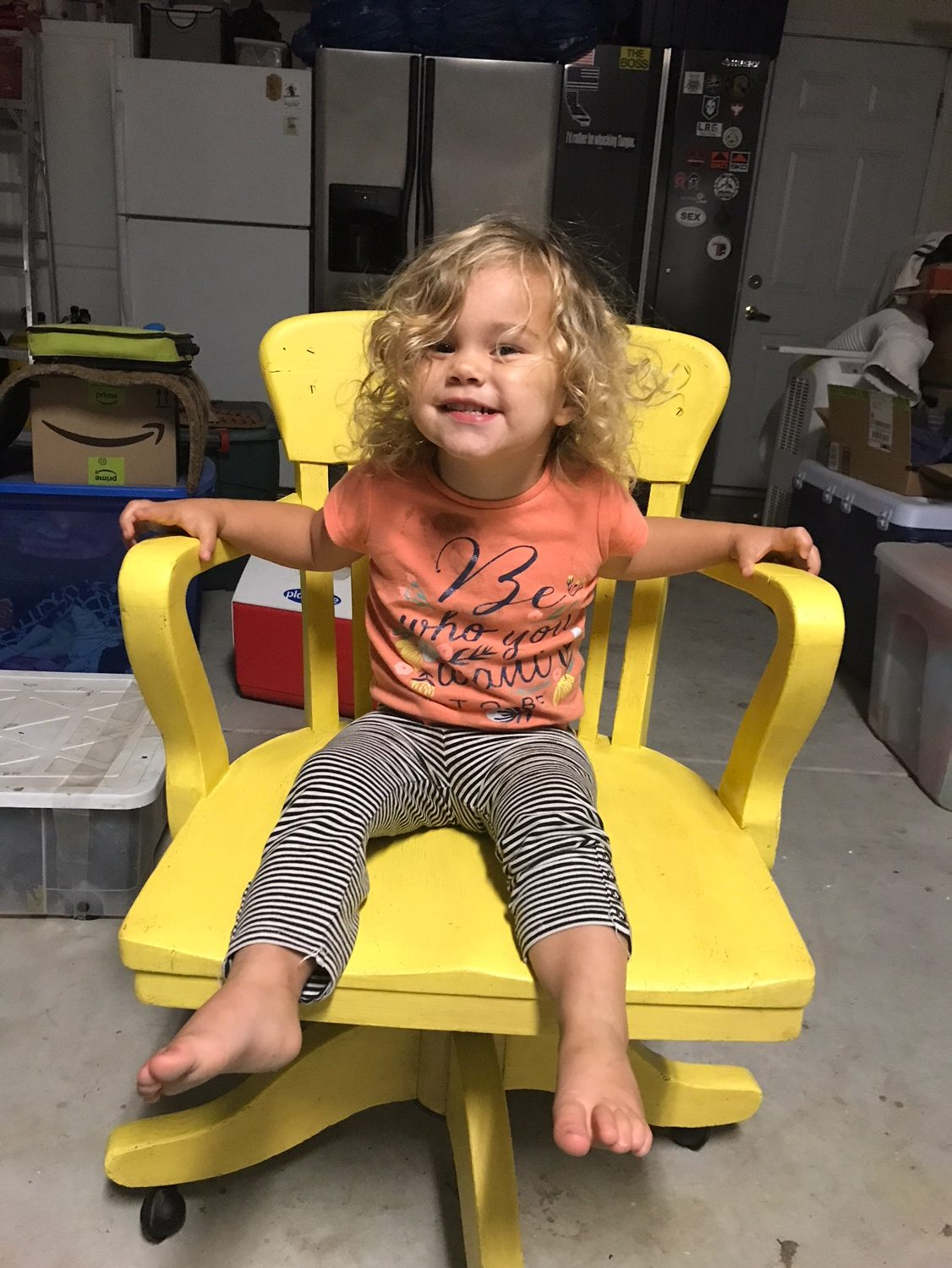 curly haired girl in yellow chair