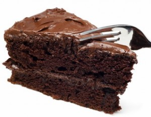Fork cutting into a slice of chocolate cake. Isolated on White.