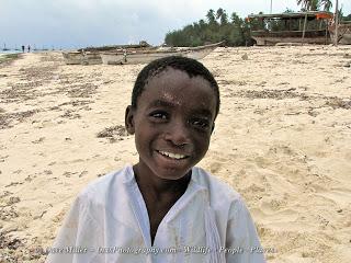 local boy on the beach in Zanzibar smiling at camera