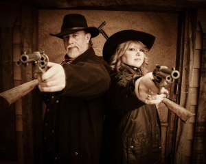 Gunslinging cowboy and cowgirl at Wild Gals Old Time Photo in Pigeon Forge TN.