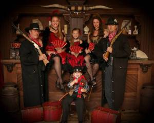 A family dressed as cowboys and saloon gals for an old time photo in Pigeon Forge TN.