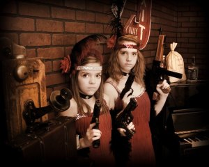 Young sisters dressed as flapper girls with guns.