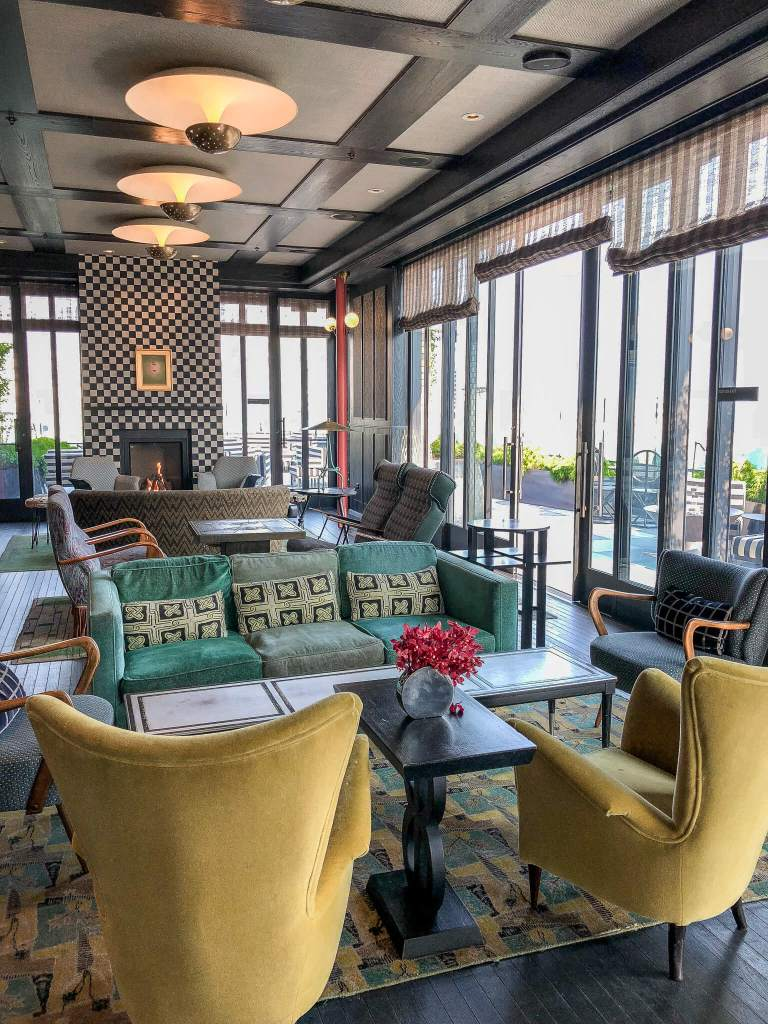 The interior at The Proper Hotel rooftop lounge is filled with mustard, aqua and grey seats alongside many different textures.