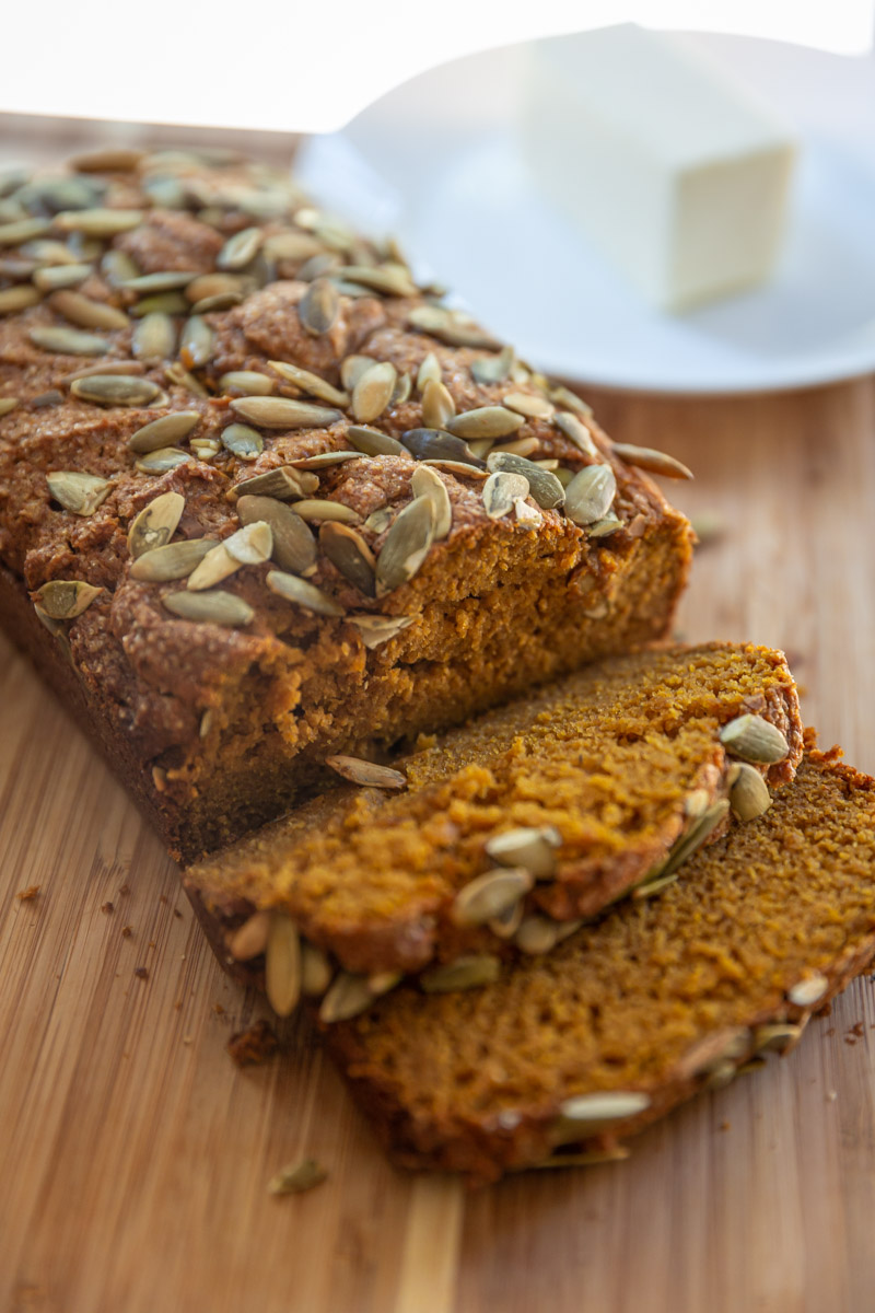 A Whole Wheat Pumpkin Bread loaf, fresh out of the oven is served with soft butter.