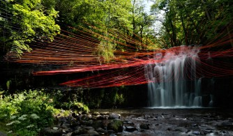 This scene is made from 300 coloured strings. They slowly end in transparency, reminiscent of droplets. The lines and vibrant red colour creates a visual effect that plays with the perceived volume of the waterfall while increasing the scenic outcome of this waterfall.