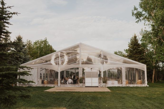 Beautiful outdoor greenhouse style wedding reception tent surrounded by kept trees