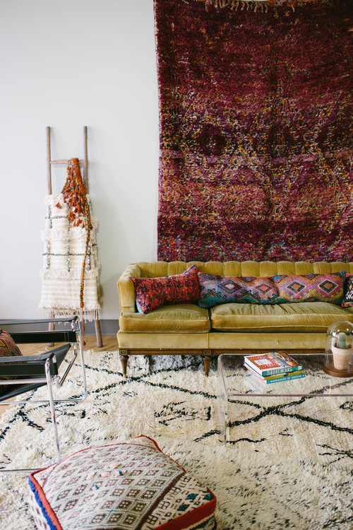 Deep red rug hung in a chic boho living room
